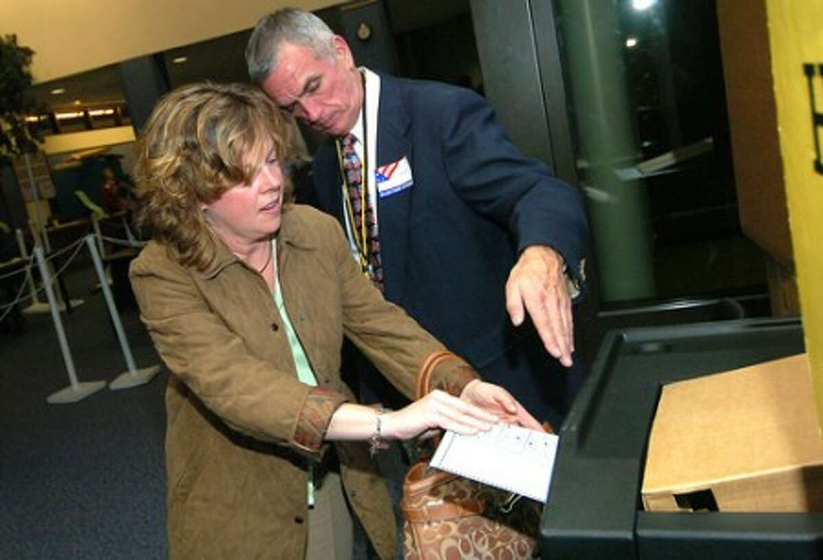 Photo/Alex von Kleydorff. Pam Keough casts her vote as Moderator James Burch shows her where to slide her ballot in during Wilton voting at District 1 at Wilton High School