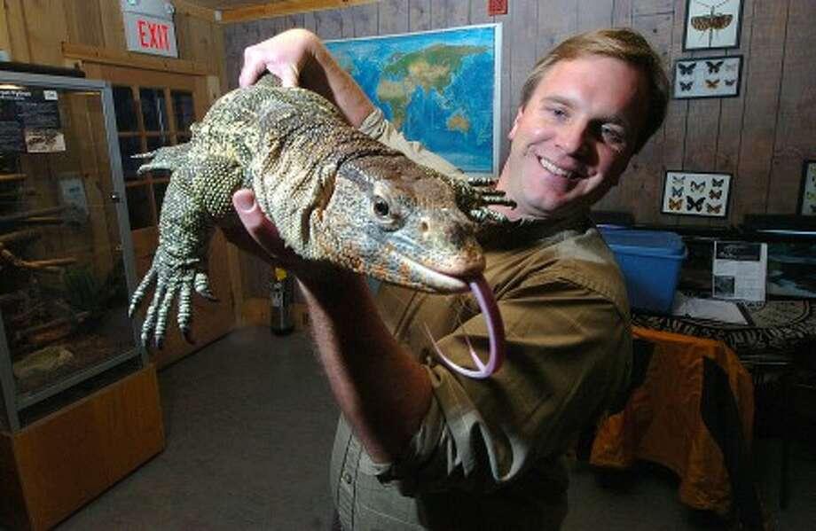 "Photo/Alex von Kleydorff. Animal Embassy Founder/Director Chris Evers presents ""Grumpy"" a Nile Monitor lizard."