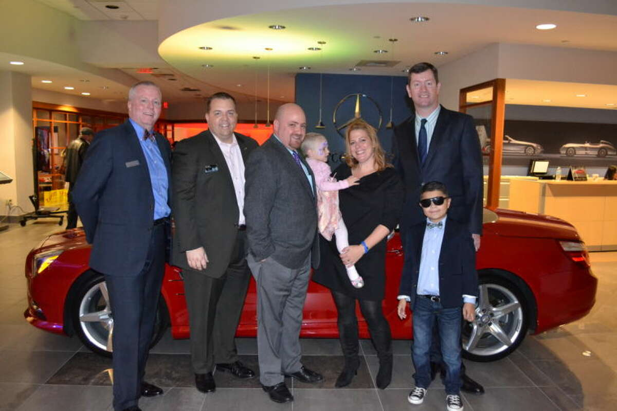 (from left to right) -Mike Burke, President and CEO of Make-A-Wish, Mark Hoch, General Manager of New Country Mercedes-Benz, Tom Ostergren, Quinn Ostergren and Alyssa Ostergren of Tolland, Tim Parker, General Manager of New Country BMW and MINI, and Christian Mercado of North Haven celebrate the miracles of the season at the Bright Lights, Bright Wishes