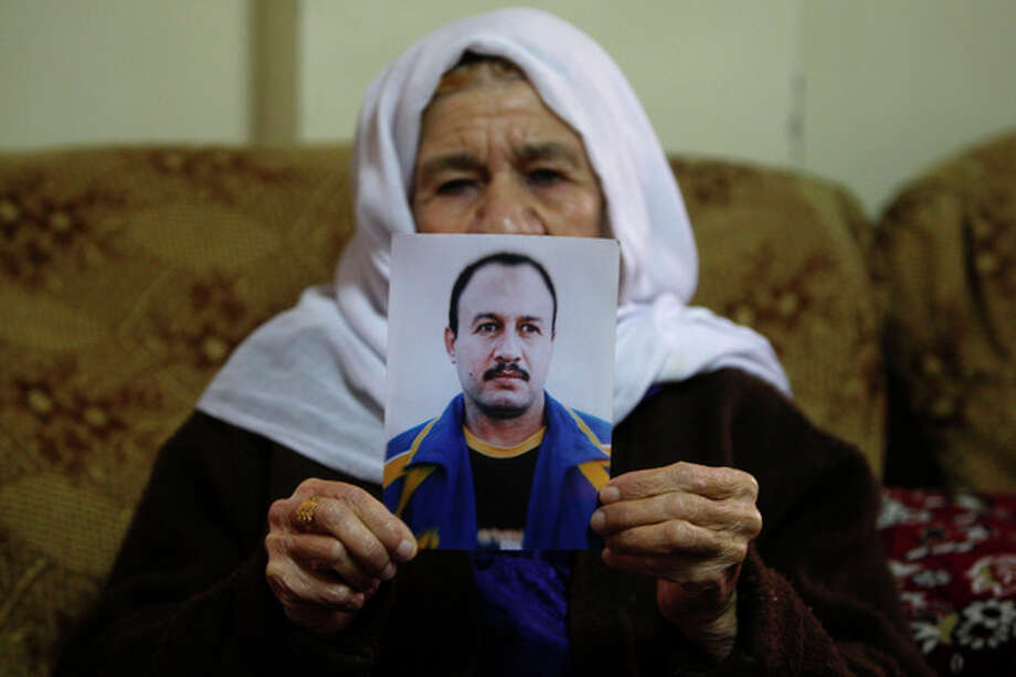 Palestinian Hassiba Shehadeh, 67, holds a picture of her son Ahmed at her home at Qalandia refugee camp near the West Bank city of Ramallah, Sunday, Dec. 29, 2013. Ahmed is one of the 26 Palestinian prisoners who were convicted in connection to the killing of Israelis, that Israel announced to release this week. (AP Photo/Majdi Mohammed) / AP