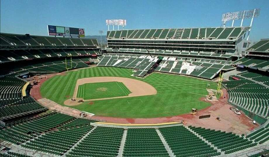 FILE -- This Aug. 7, 1996, file photo, shows the Oakland Coliseum in transition from baseball to football field configuration in Oakland, Calif. Oakland is desperately trying to keep the team from moving out of a city already struggling with crime, financial woes and blow after blow to its public image. To the south in the heart of booming Silicon Valley, San Jose is seeking to bolster its profile and treasury with an aggressive campaign to win the A's, including a legal challenge to Major League Baseball's sacrosanct antitrust exemption that the mayor vows to take to the U.S. Supreme Court if necessary. Standing in the way are San Francisco's Giants, who claim the lucrative Silicon Valley commercial market as their exclusive territory. And so far, the Giants are winning. (AP Photo/Ben Margot, File) / AP