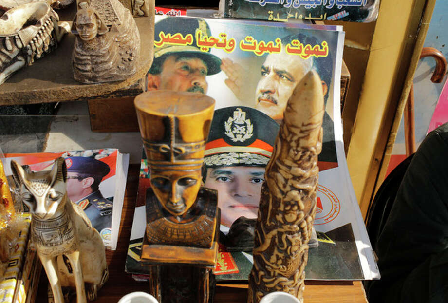 "A poster showing Defense Minister Gen. Abdel-Fattah el-Sissi, center, late Presidents Gamal Abdel-Nasser, top right, and Anwar Sadat, top left, is displayed with souvenirs of Egypt's Pharaonic monuments at a shop in Cairo, Egypt, Saturday, Dec. 28, 2013. Arabic reads, ""we die but Egypt lives."" (AP Photo/Amr Nabil) / AP"