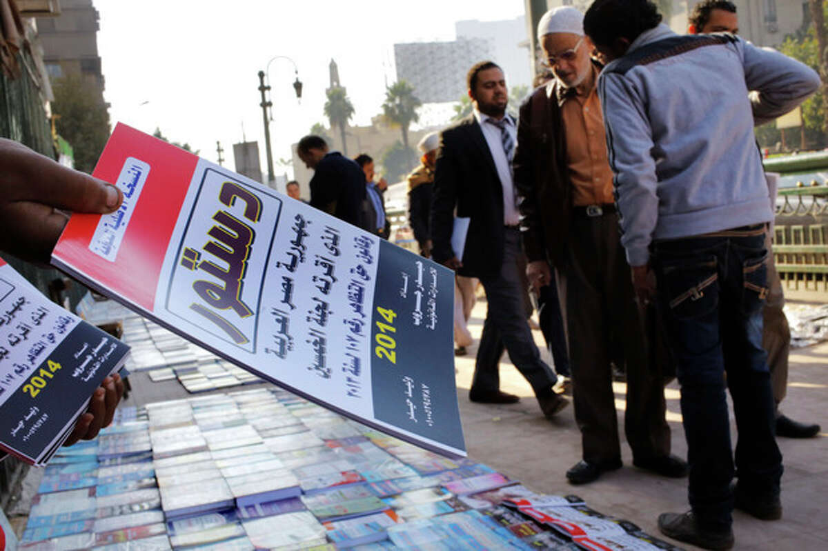 An Egyptian vender sells copies of the new constitution in Cairo, Egypt, Saturday, Dec. 28, 2013. A constitutional referendum in planned on Jan. 14 and 15. Arabic reads,