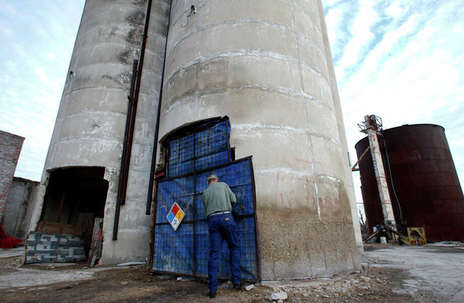 Robert Payne, operator of RPA Associates secures a door latch on a grain silo that he uses as a storage facility for ammonium nitrate, Thursday, Dec. 12, 2013, in Clifton, Texas. Payne said he didn't worry about safety before or after the West explosion, and met with local volunteer firefighters afterward to discuss what to do in an emergency. (AP Photo/Tony Gutierrez) / AP