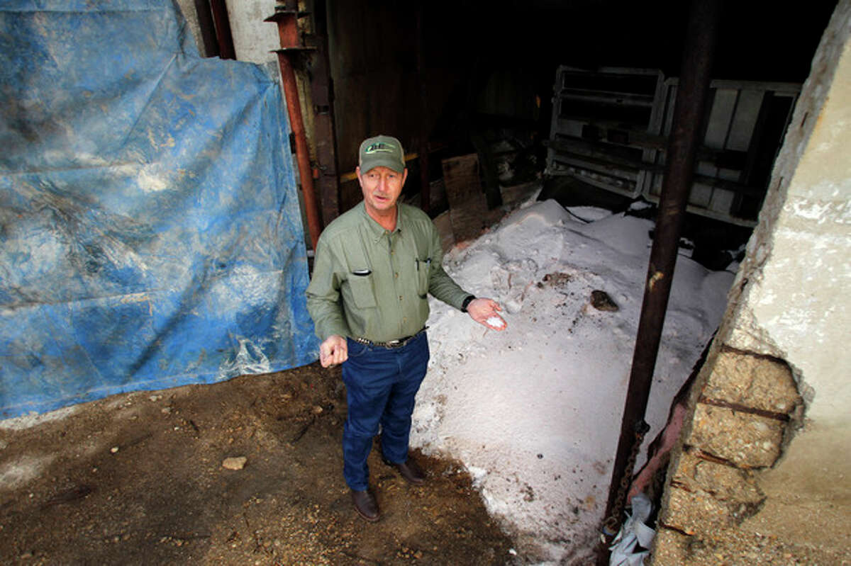 Robert Payne describes the texture of ammonium nitrate as he stands by a pile of the product, Thursday, Dec. 12, 2013, in Clifton, Texas. Payne runs RPA Associates, where he keeps ammonium nitrate inside a tall concrete silo once used for grain. (AP Photo/Tony Gutierrez)