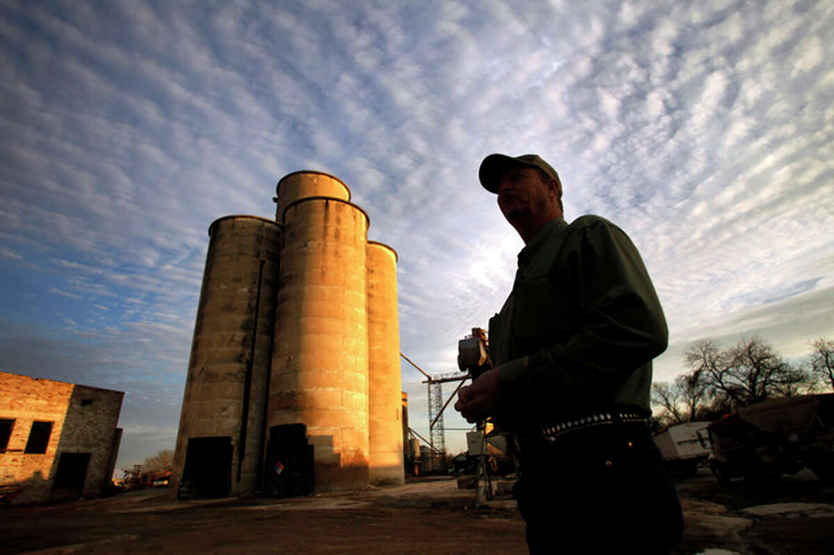 Robert Payne stands on his business property as he talks with a reporter, Thursday, Dec. 12, 2013, in Clifton, Texas. Payne runs RPA Associates, where he keeps ammonium nitrate inside a tall concrete silo once used for grain. (AP Photo/Tony Gutierrez)