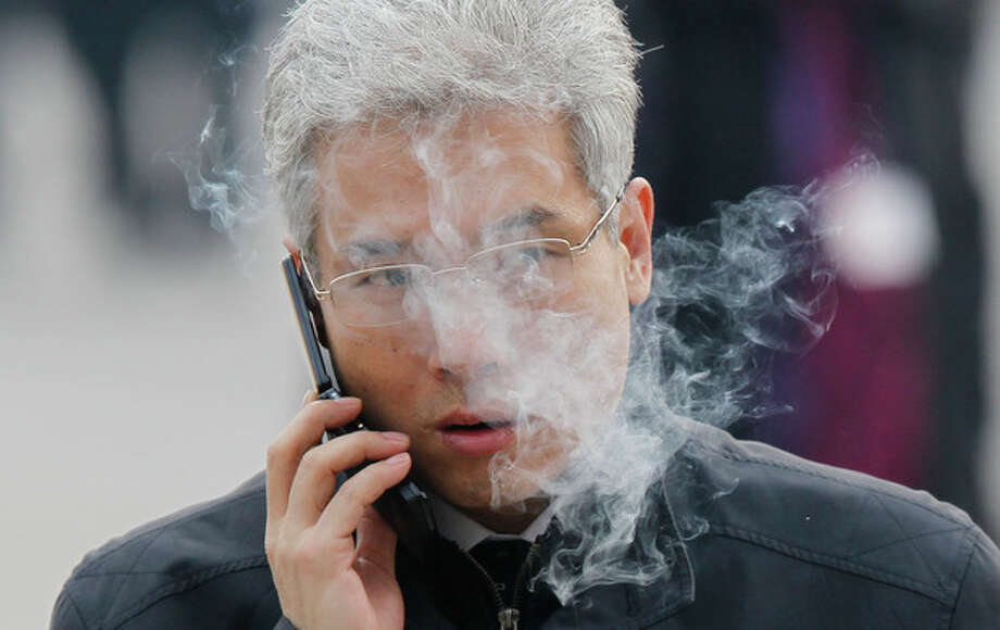 In this photo taken Sunday, March 4, 2012, a man smokes as he walks with other delegates attending a meeting at the Great Hall of the People in Beijing, China. China has banned its officials from smoking in public to set an example to the rest of the country that has the world's largest number of smokers. China's state media said Sunday, Dec. 29, 2013 that officials are not allowed to smoke in schools, hospitals, sports venues, on public transport or any other places where smoking is banned, or to smoke or offer cigarettes when performing official duties. (AP Photo/Ng Han Guan) / AP