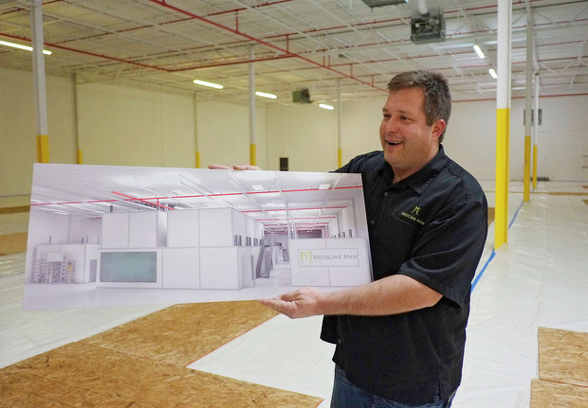 In this Dec. 5, 2013, photo, Pete Williams holds a drawing of the new grow facility that is being built at the Medicine Man dispensary and grow operation in northeast Denver. A gleaming white Apple store of weed is how Pete Williams sees his new Denver marijuana dispensary. Two floors of pot-growing rooms will have windows showing the shopping public how the mind-altering plant is grown. Shoppers will be able to peruse drying marijuana buds and see pot trimmers at work separating the valuable flowers from the less-prized stems and leaves.(AP Photo/Ed Andrieski)