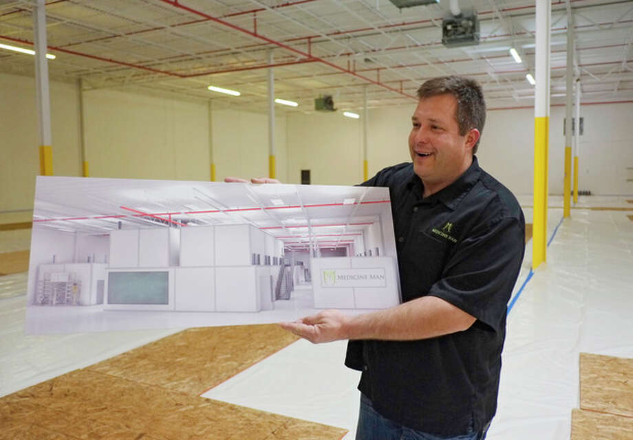 In this Dec. 5, 2013, photo, Pete Williams holds a drawing of the new grow facility that is being built at the Medicine Man dispensary and grow operation in northeast Denver. A gleaming white Apple store of weed is how Pete Williams sees his new Denver marijuana dispensary. Two floors of pot-growing rooms will have windows showing the shopping public how the mind-altering plant is grown. Shoppers will be able to peruse drying marijuana buds and see pot trimmers at work separating the valuable flowers from the less-prized stems and leaves.(AP Photo/Ed Andrieski) / AP