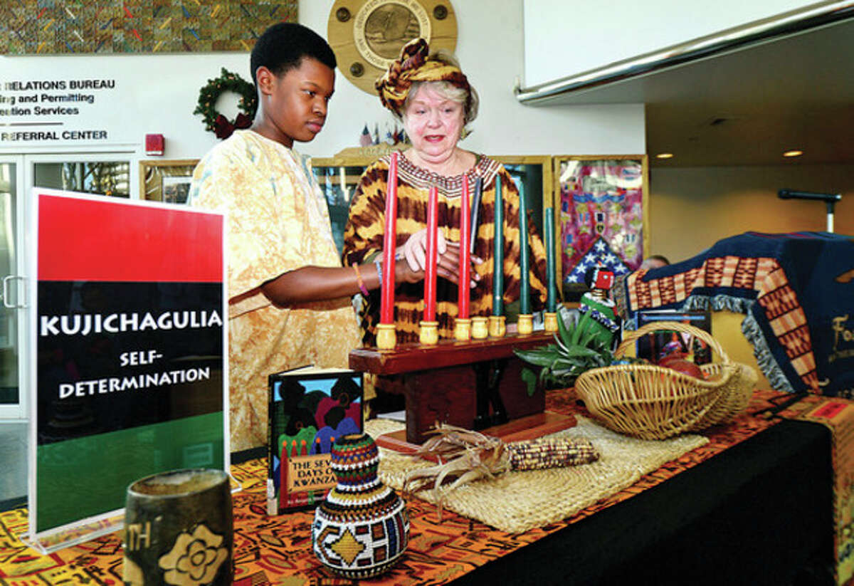 Christian Colvin and Judy Rochon participate in Stamford's 19th annual Mayor's Kwanzaa Celebration at the Stamford Government Center Friday.