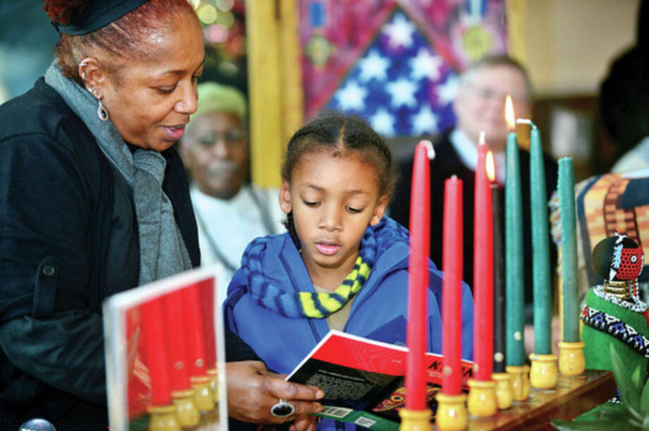 Charlene Fuller and Tavon Maple participate in Stamford's 19th annual Mayor's Kwanzaa Celebration at the Stamford Government Center Friday. / (C)2013, The Hour Newspapers, all rights reserved