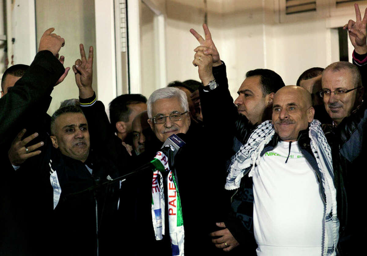Palestinian President Mahmoud Abbas, center, receives released Palestinian prisoners during a welcome ceremony after their arrival at the Palestinian headquarters in the West Bank city of Ramallah, Tuesday, Dec. 31, 2013. Israel released more than two dozen Palestinian prisoners convicted in deadly attacks against Israelis early Tuesday as part of a U.S.-brokered package to restart Mideast peace talks. (AP Photo/Nasser Nasser)