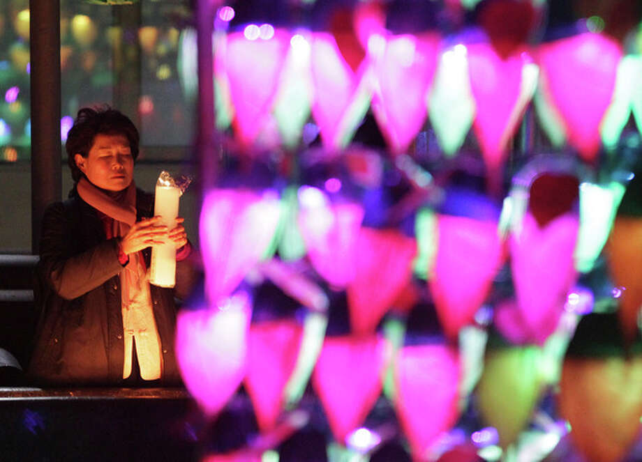 A Buddhist woman holding a candle light prays ahead of the new year at Chogye Buddhist temple in Seoul, South Korea, Tuesday, Dec. 31, 2013. (AP Photo/Ahn Young-joon) / AP
