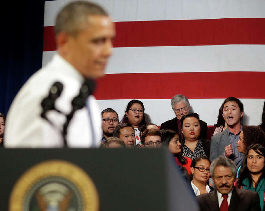 """FILE - In this Nov. 25, 2013 file photo, President Barack Obama, left, stops his speech and turns around in response to an unidentified man, right, who heckled him about anti-deportation policies, at the Betty Ann Ong Chinese Recreation Center in San Francisco. Obama stopped his speech about immigration reform to let this man, who was located directly behind Obama, speak and would respond to his questions. It was a moment for Barack Obama to savor. His second inaugural address over, Obama paused as he strode from the podium last January, turning back for one last glance across the expanse of the National Mall, where a supportive throng stood in the winter chill to witness the launch of his new term. """"I want to take a look, one more time,"""" Obama said quietly. """"I'm not going to see this again.""""There was so much Obama could not _ or did not _ see then, as he opened his second term with a confident call to arms and an expansive liberal agenda. (AP Photo/Pablo Martinez Monsivais, File) / AP"""