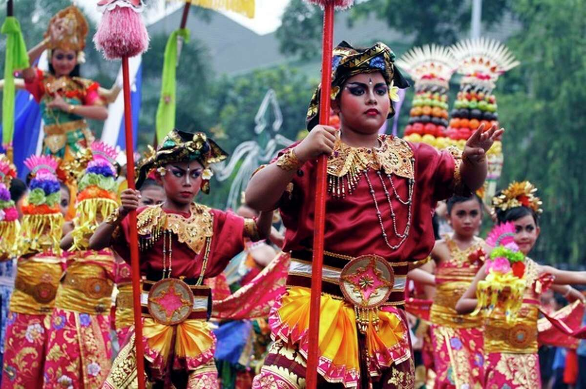 Balinese children wearing traditional costumes dance during a parade for this year's last sundown in Bali island, Indonesia on New Year's Eve, Tuesday, Dec. 31, 2013. (AP Photo/Firdia Lisnawati)