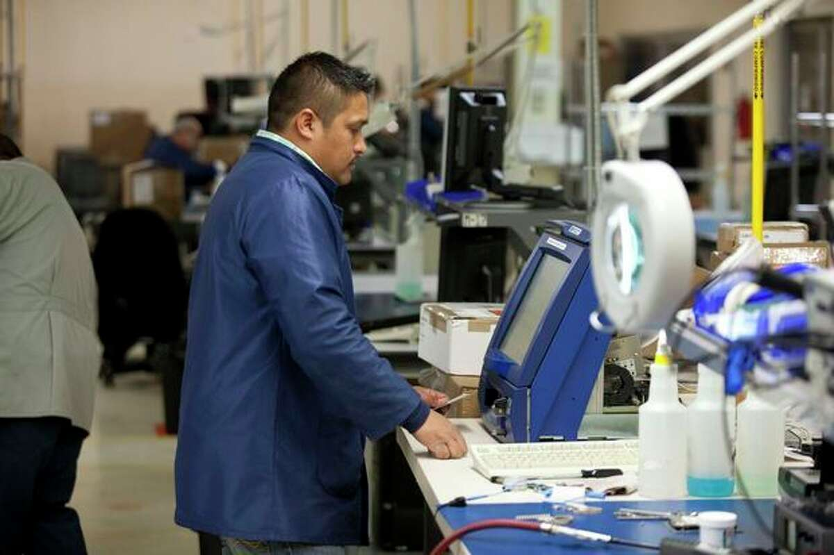 In this Friday, Dec. 27, 2013 photo, a factory worker tries to fix an ATM card reader at a maquiladora belonging to the TECMA group in Ciudad Juarez, Mexico. With the implementation of the North American Free Trade Agreement twenty years ago, many North American and international companies have moved their manufacturing to Mexico at a lower cost. While there is undoubtedly a larger middle class today, Mexico is the only major Latin American country where poverty also has grown in recent years. (AP Photo/Ivan Pierre Aguirre)