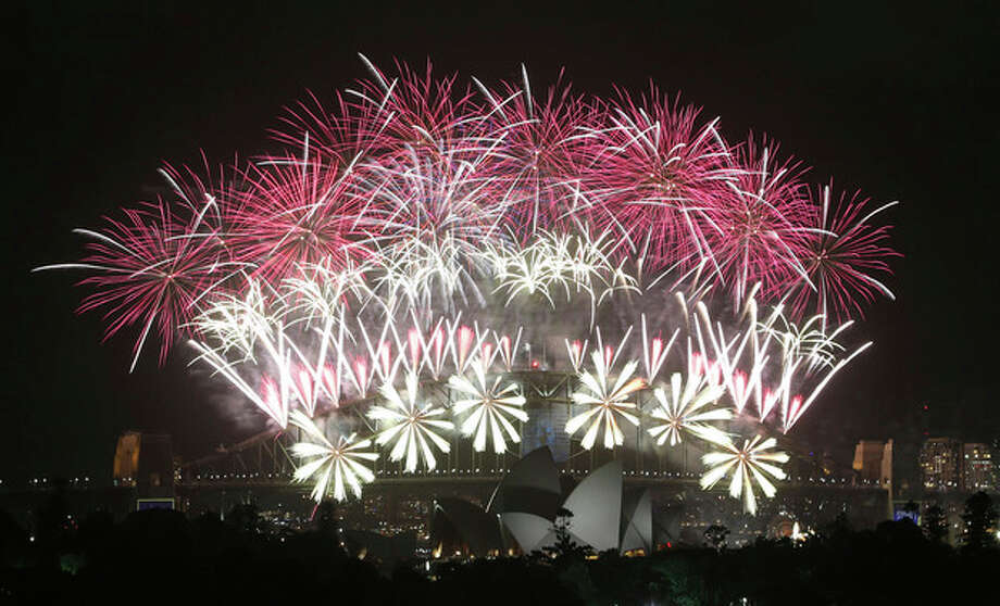 Fireworks explode over the Harbour Bridge and the Opera House during New Year's Eve celebrations in Sydney, Australia, Wednesday, Jan. 1, 2014. (AP Photo/Rob Griffith) / AP