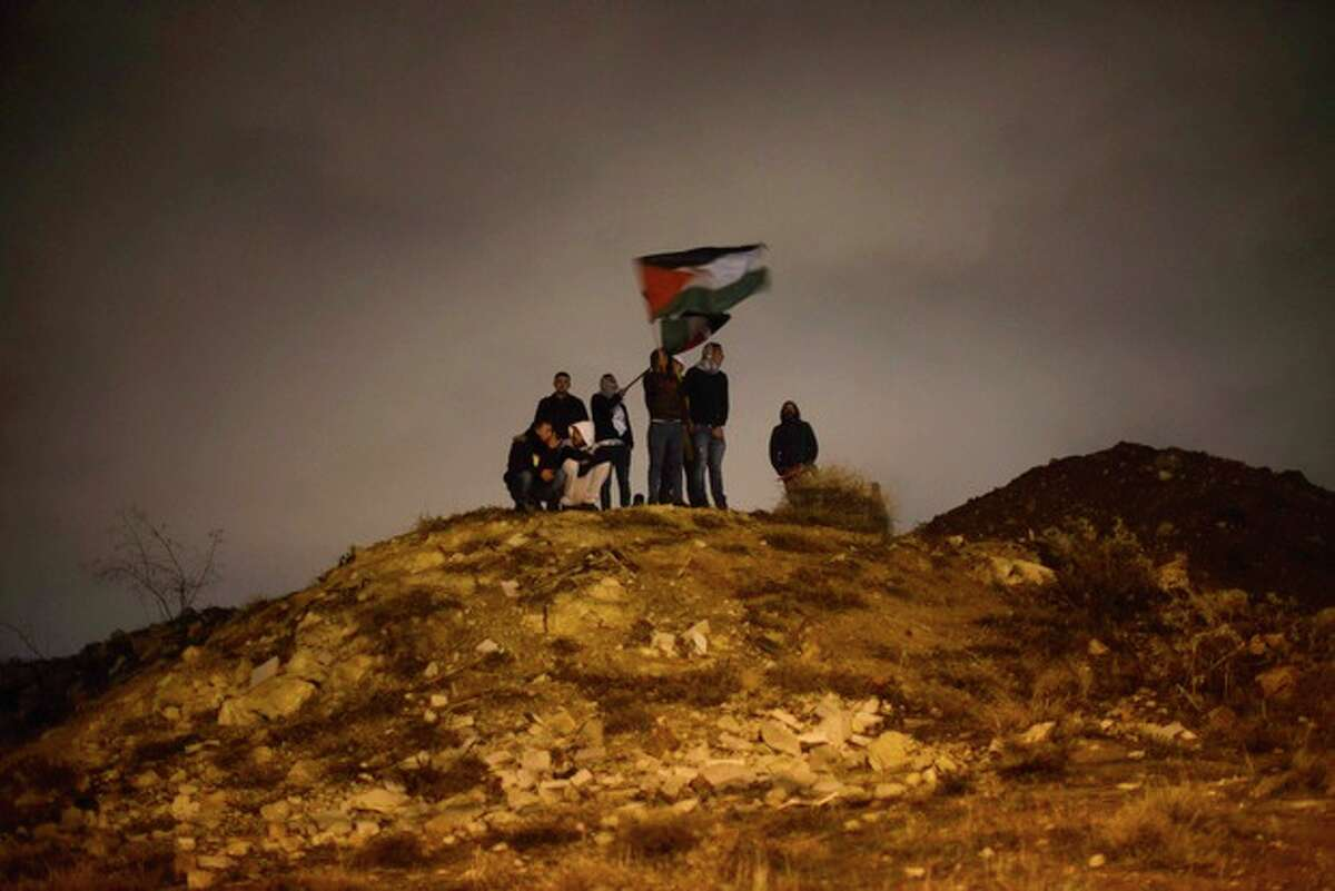 Palestinians wave their national flag as they await the release of Palestinian prisoners in Jerusalem, Tuesday, Dec. 31, 2013. Israel released more than two dozen Palestinian prisoners convicted in deadly attacks against Israelis early Tuesday as part of a U.S.-brokered package to restart Mideast peace talks. (AP Photo/Mahmoud Illean)