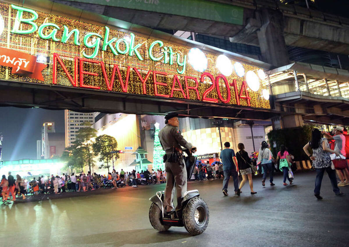 A Thai police officer patrols as people start to gather on a street outside the Central World shopping mall to celebrate the New Year in Bangkok, Thailand, Tuesday, Dec. 31, 2013. (AP Photo/Apichart Weerawong)