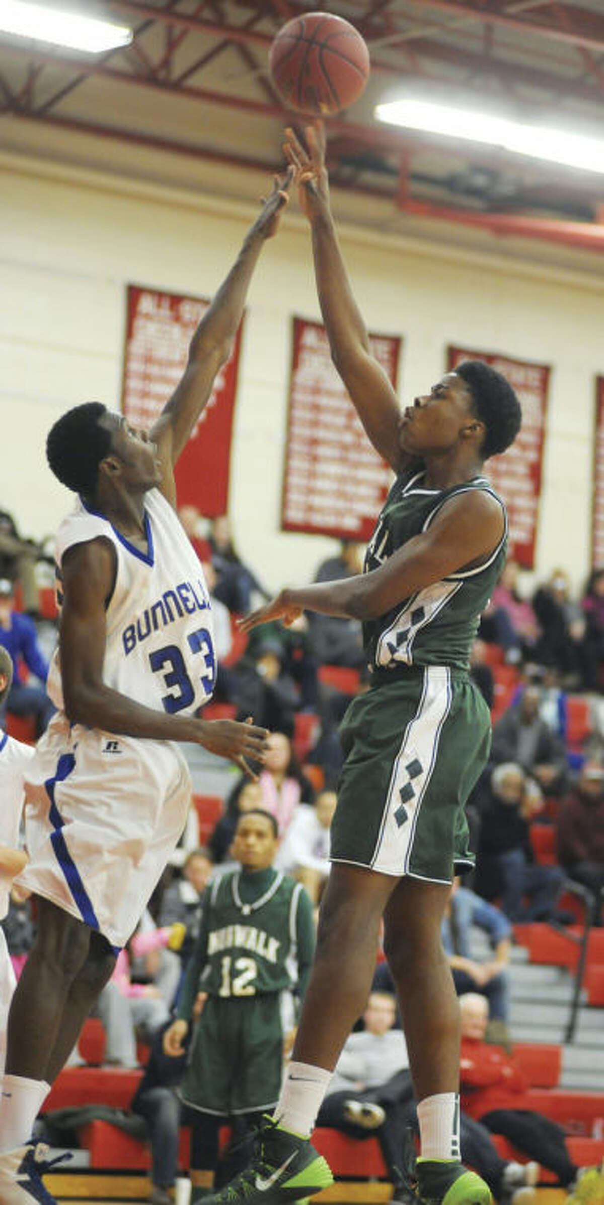 Hour photo/John Nash Norwalk's Steven Enoch puts up a soft jumper over the defense of Bunnell's Romklyns Joseph during Monday's championship game of the Masuk Holiday Tournament.