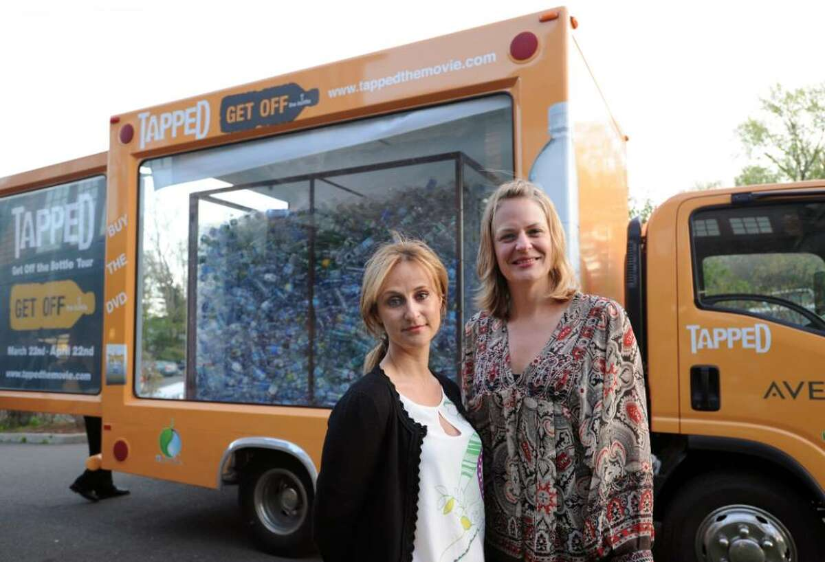 """Stephanie Soechtig, left, and Sarah Olson, the director and producer of the anti-bottled water documentary """"Tapped,"""" respectively, posed in front of their promotional vehicle for their film outside Audubon Greenwich, Friday evening, April 23, 2010. The pair were at the Audubon for the screening of their film, which warns of the the harmful effects that the bottled water industry has on humans, animals and the environment."""