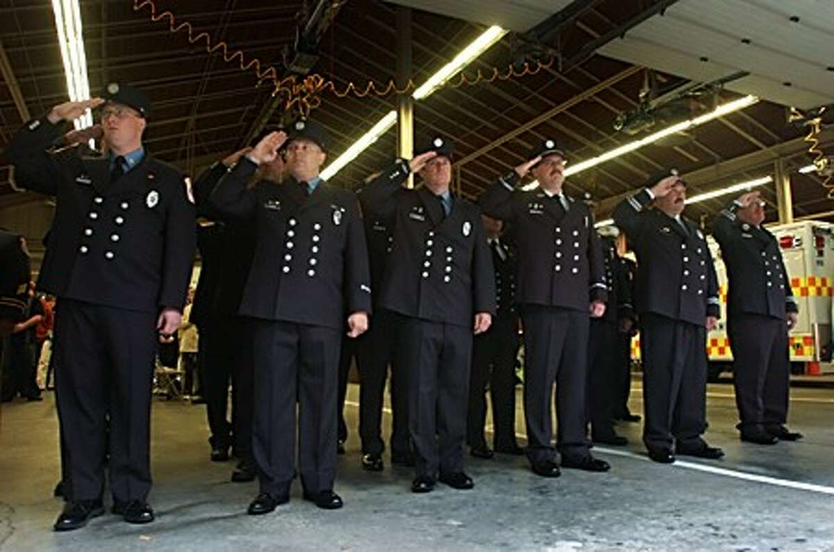 Wilton firefighters salute as the flag was raised to half mast during the 9-11 remembrance ceremony at Wilton Fire Headquarters Friday. Hour photo / Erik Trautmann