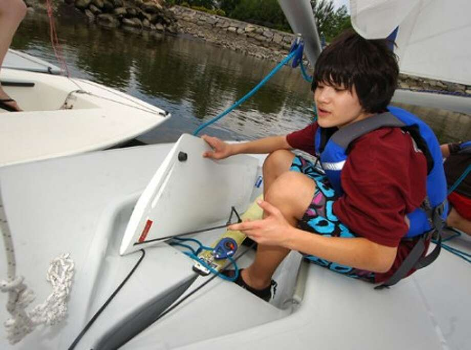 Photo/Alex von Kleydorff. 13 yr old Rainer Moy-Huwyler prepares his sailbout during Stamford Sailing Foundation''s Blue Water Bound program at Southfield Beach