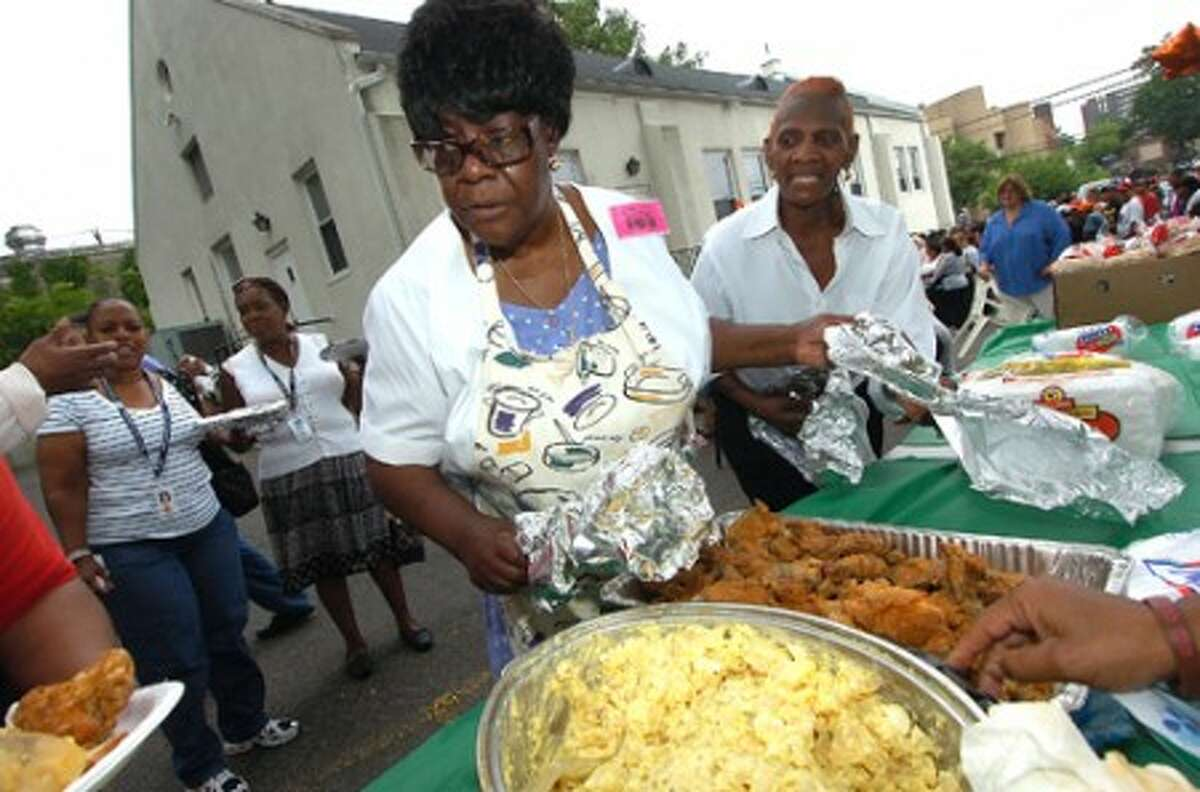 Photo/Alex von Kleydorff. Joyce Gumbus, pantry Coordinator with the Wilson Food Pantry, sets out hot fresh food for all to enjoy as the pantry celebrates its fourth year anniversary in Stamford.