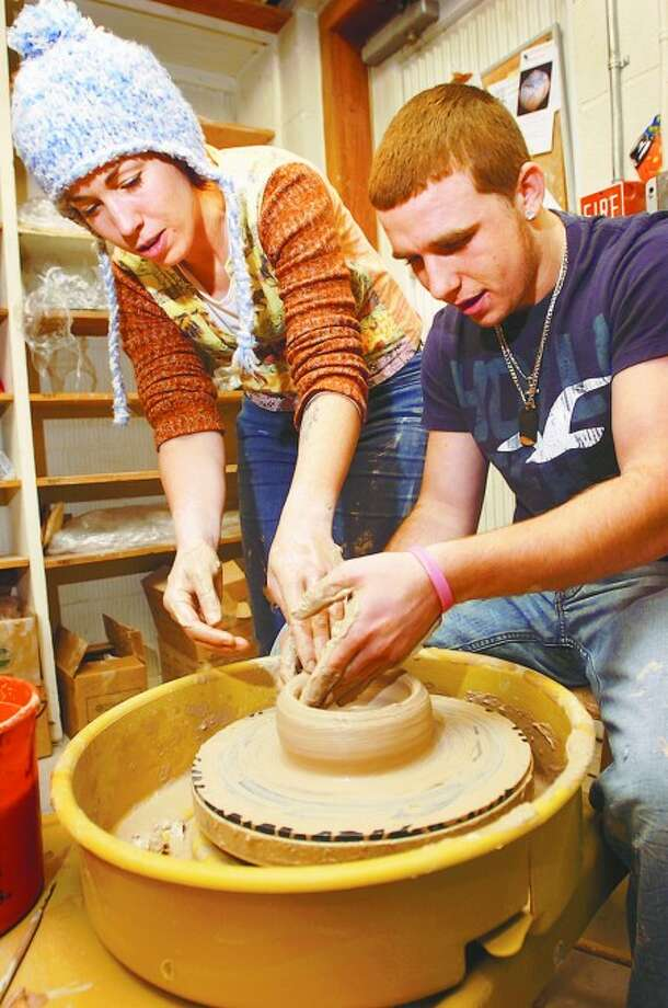 Silvermine Arts Guild studio manager Heather Houston assists Briggs High school student Nick Falcone during the schools pottery workshop Tuesday. Hour photo / Erik Trautmann