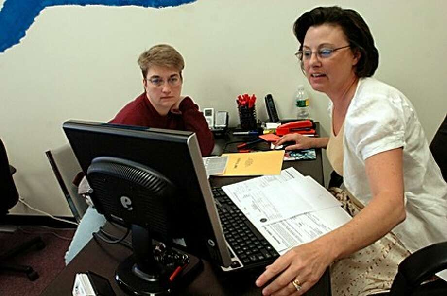 Liberty Tax Service employee, Denise Vasquez helps out Kathy Russell with her taxes on Tuesday with just days left before the deadline/hour photo matthew vinci