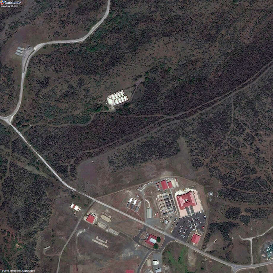 This satellite image provided by TerraServer.com and DigitalGlobe shows an image captured on Sept. 2, 2010, shows a portion of Naval Station Guantanamo Bay, Cuba, including the secret facility known as Penny Lane, upper middle in white. In the early years after 9/11, the CIA turned a handful of prisoners at the secret facility into double agents and released them. Current and former U.S. officials tell The Associated Press that the program helped kill terrorists. The program was carried out in the secret facility, built a few hundred yards from the administrative offices of the prison in Guantanamo Bay, bottom of image. The eight small cottages were hidden behind a ridge covered in thick scrub and cactus. (AP Photo/TerraServer.com and DigitalGlobe) / TerraServer.com and DigitalGlobe