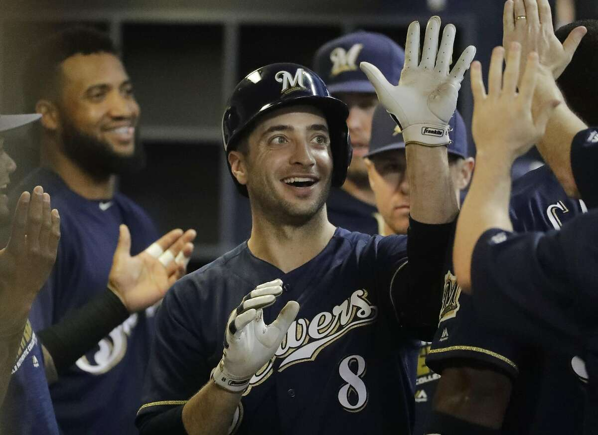 Milwaukee Brewers' Ryan Braun is congratulated in the dugout after hitting a single during the sixth inning of a baseball game against the Oakland Athletics Tuesday, June 7, 2016, in Milwaukee. The hit was Braun's 1,500 career hit. (AP Photo/Morry Gash)