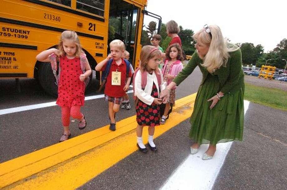 Photo/Alex von Kleydorff. Miller pricipal Cheryl Jensen-Gerner helps first day Miller School students find their way off the buses.