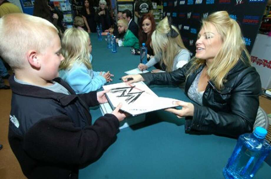 Photo/Alex von Kleydorff. 8 yr old Kevin Brugger from Trumbull gets a WWE book signed by Beth Phoenix after dropping a toy in the bin for Toys for Tots at Tommy k''s in Stamford