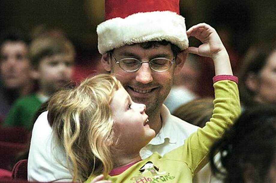 Merlin Meyer-Mitchell and his daughter Nina 3, enjoying Holiday music at the annual Norwalk City Hall tree lighting in the concert hall on Wednesday night/hour photo matthew vinci