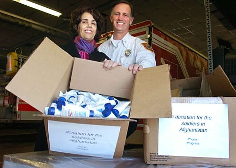 Jane Definis and Captain Ed Prescott display some of the skin care products Beiersdorf Inc. donated to U.S. soldiers in Afghanistan. Definis, a former Norwalk resident, spearheaded the donation drive. Prescott, Norwalk Fire Department captain, facilitated temporary storage of items at Broad River Fire Station. Hour photo / Erik Trautmann
