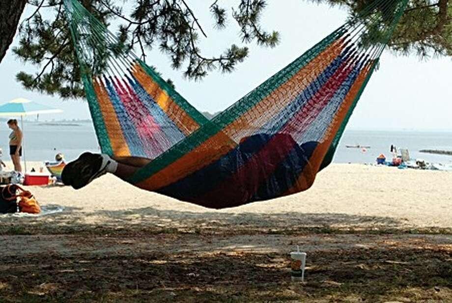 A beach-goer beats the heat Monday afternoon in a hammock at Calf Pasture Beach/hour photo matthew vinci