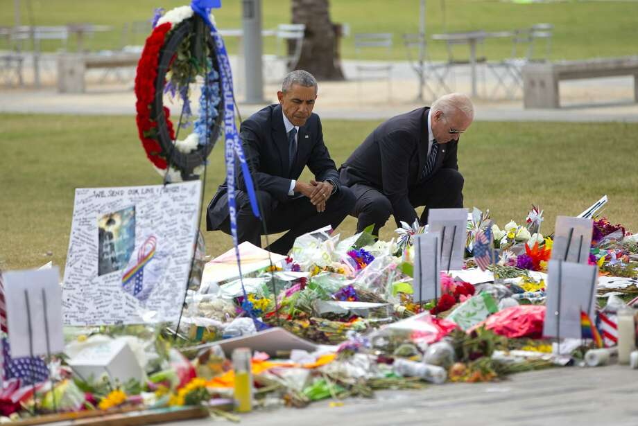 President Barack Obama and Vice President Joe Biden visit a memorial to the victims of the Pulse nightclub shooting, Thursday, June 16, 2016 in Orlando, Fla. Offering sympathy but no easy answers, Obama came to Orlando to try to console those mourning the deadliest shooting in modern U.S history. Photo: Pablo Martinez Monsivais/AP