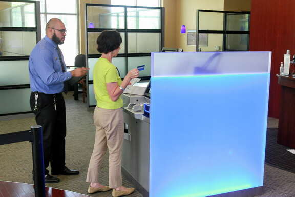 Customer Nicole Dijak gets some help from bank teller Mark Flores, while using one of the new generation ATMs in the Chase lobby at the Washington and Studemont branch. (For the Chronicle/Gary Fountain, May 13, 2016)