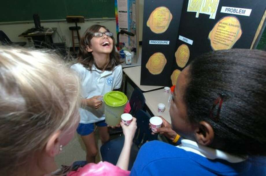 Photo/Alex von Kleydorff. All Saints School 5th grader Erika Rosendahl laughs at the reaction her classmate test subjects have after tasting a sample of lemonade . Her second place winning project ''Lemony Line-up'' was a taste test of three diffferent types of lemonade.