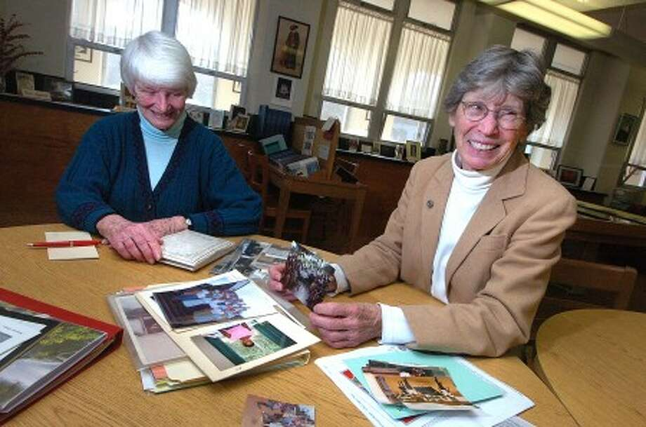 Photo/Alex von Kleydorff. L-R School Sisters of Notre Dame Laurellen Nixon and Loreen Spaulding sort through old photos from their time in Africa as missionaries with order.