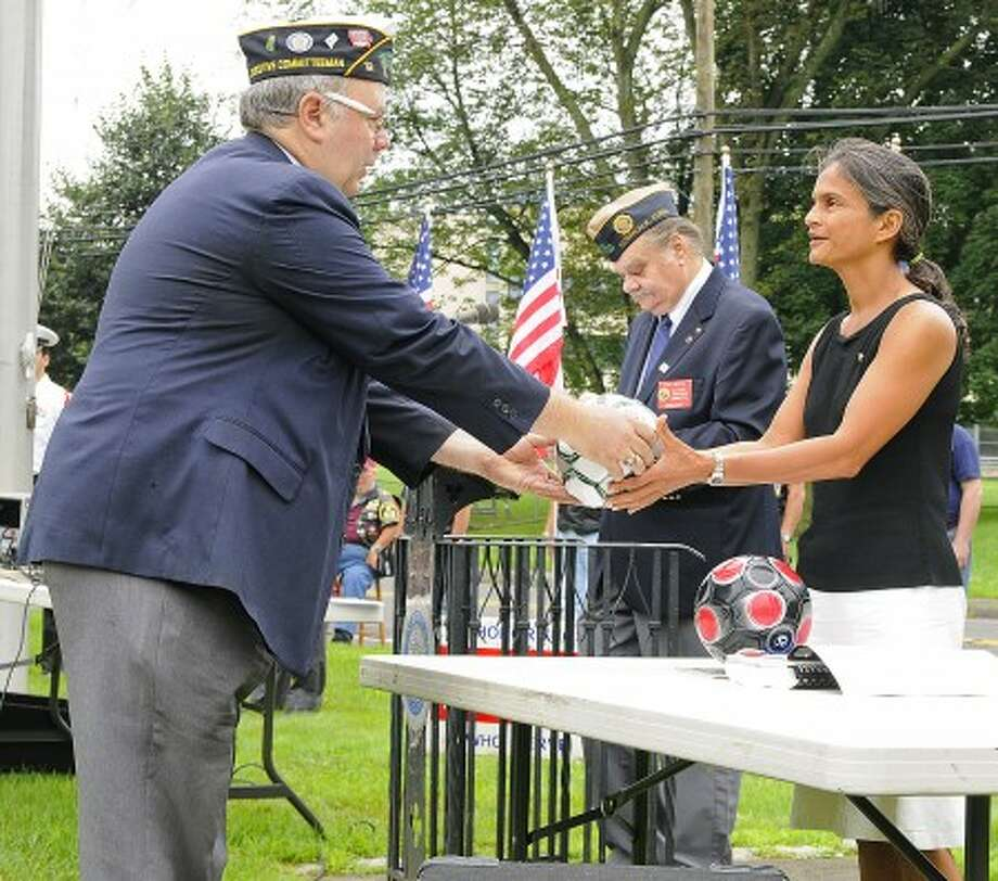 """Richard Olson, commander of American Legion Post 12, hands a soccer ball to Shalini Madaras, mother of Army PFC Nicholas A. Madaras, who died in Iraq in September 2006. Ten soccer balls provided by the Norwalk Veterans Memorial Committee were donated to Madaras'' family for its """"Kick for Nick"""" program, which has sent more than 23,000 soccer balls to Iraqi children."""