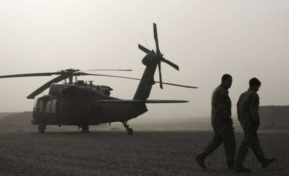 U.S. Army air crew members walk past a Black Hawk helicopter used by Task Force Pegasus for medevac missions, at a forward operating base Helmand province, southern Afghanistan, Sunday Feb. 14, 2010. TF Pegasus crews have come under fire daily while on missions supporting U.S. and Afghan troops taking part in an ongoing assault in the Taliban-held town of Marjah. (AP Photo/Brennan Linsley)