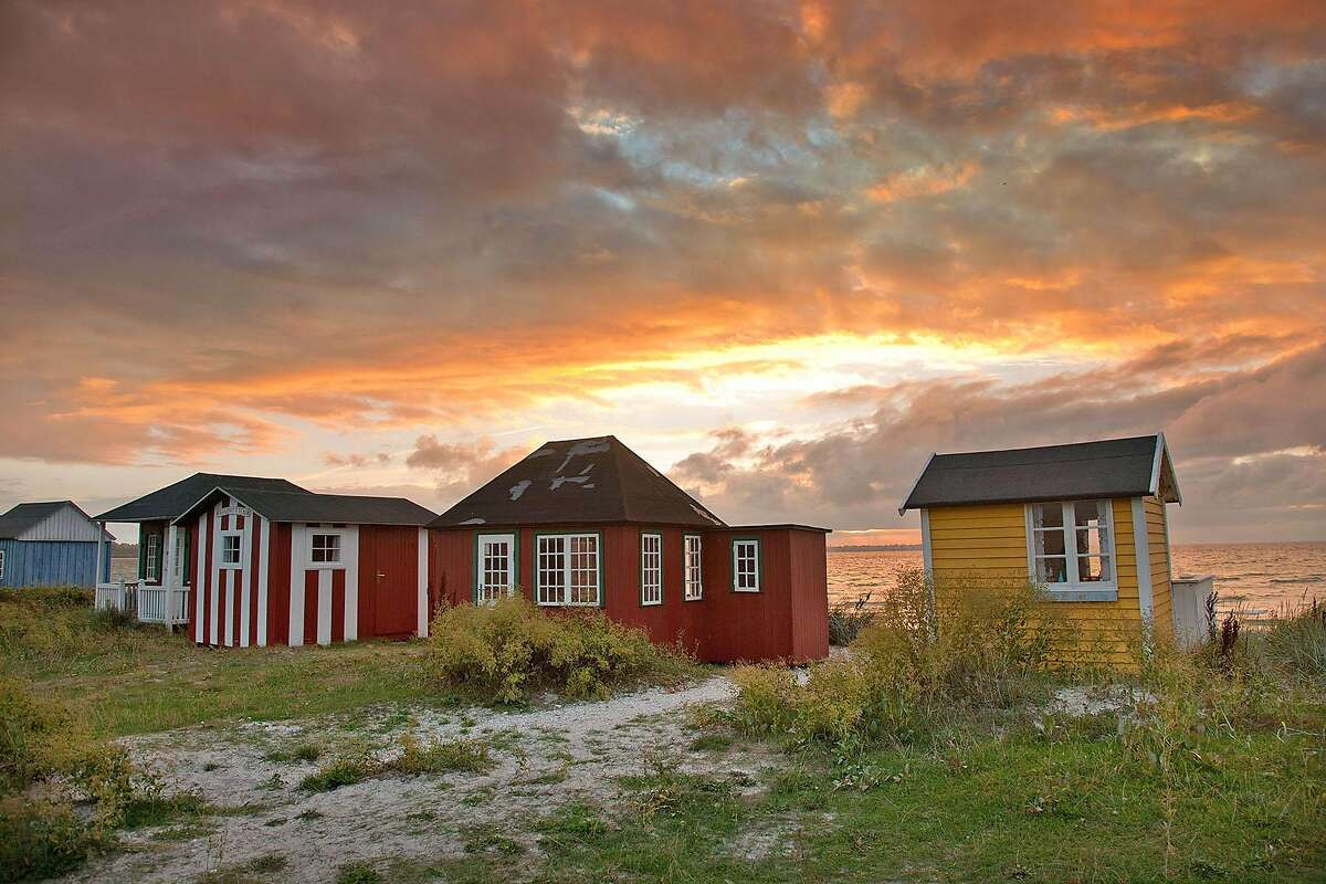 On Denmark�s Aero Island, a row of tiny huts � each different, but all stained with merry memories of locals enjoying themselves Danish-style � faces the sunset.