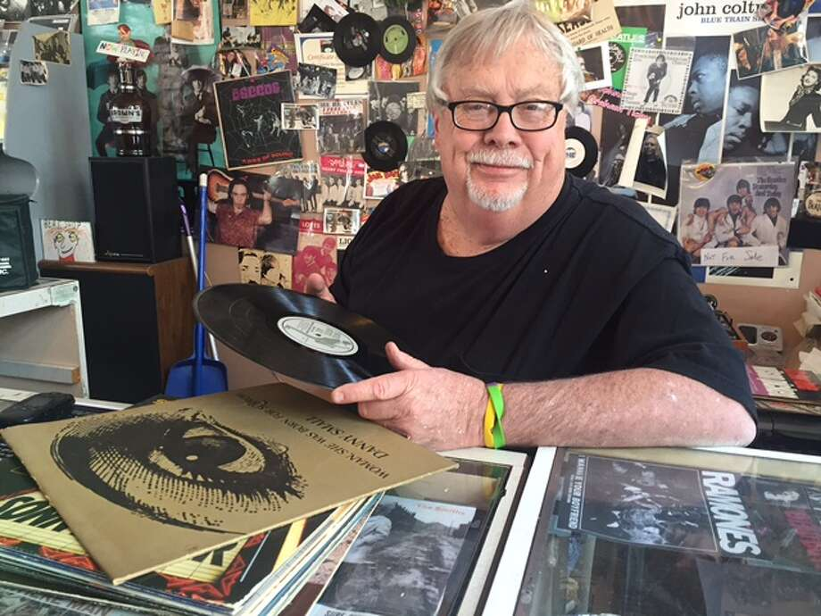 Jim Barret, an owner of The River Street Beat Shop, inspects a used record to purchase for his shop. credit: Caitlin Jansson