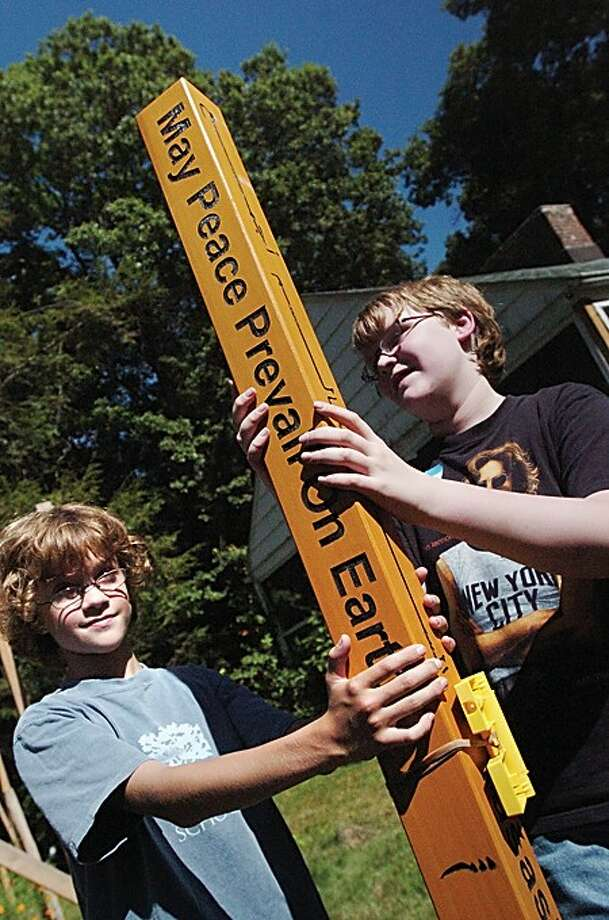 "7th graders Sam Zaref of Norwalk and William Street of Wilton help plant the Peace Pole at the CT Friends school International Peace Day on Monday. ""May Peace Prevail On Earth"" is written in eight languages on the pole/hour photo matthew vinci"