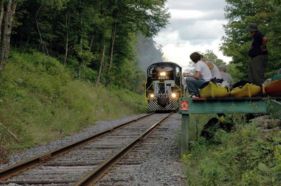 =** FOR IMMEDIATE RELEASE **Canoeists watch the  Adirondack Scenic Railroad train  arrive at a platform above whitewater on the Moose River outside Old Forge, N.Y.,  on  Aug. 26, 2006. After a couple of hours of paddling,  the paddlers would emerge from a stretch of whitewater several miles downstream and carry their boats up a steep trail to wait on a wooden platform for the train to return and carry them back upriver. (AP Photo/Mary Esch) Photo: MARY ESCH / AP