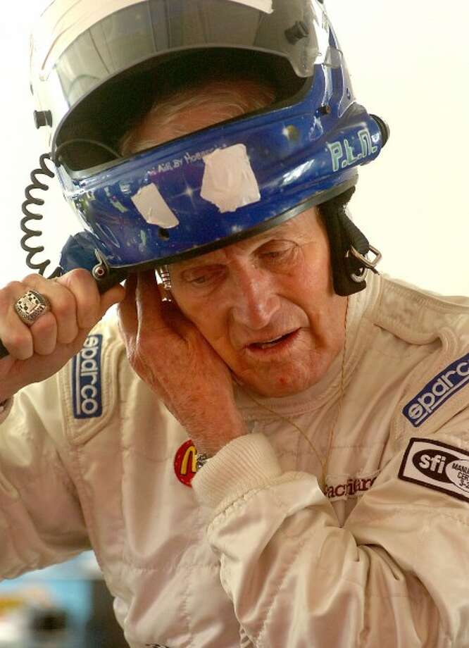 Photo/Alex von Kleydorff. Paul Newman puts on his helmet before qualifiying the #80 Corvette during the American GT Race at Lime Rock park in Lakeville CT in October of 2005