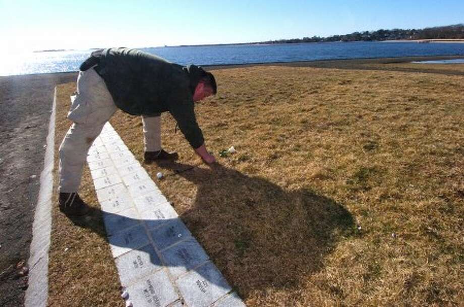 Photo/Alex von Kleydorff. A single white rose in memory of Bevery Eckert from Stamford CT, who was killed in the commuter plane crash in Buffalo NY, is placed by a park employee over the marker of her husband, Sean Rooney a victim of 911, at the Connecticut 911 memorial at Sherwood island Park in Westport on Friday afternoon.