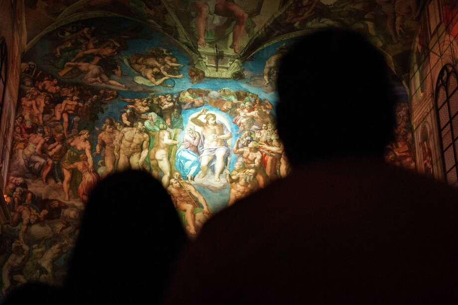 Visitors look at a reproduction of Michelangelo's Last Judgment in a replica of the Sistine Chapel in Mexico City, Thursday, June 9, 2016. A private art project has created a temporary replica of the chapel in Mexico's art deco Monument to the Revolution. The Vatican-approved Mexican replica was created using more than 2.7 million photographs printed on cloth and hung from a metal framework. The replica not only includes the frescos of Michelangelo, but sculptures and decorations also adorn the life-size model. (AP Photo/Nick Wagner) ORG XMIT: MXNW102 Photo: Nick Wagner / Copyright 2016 The Associated Press. All rights reserved. This m